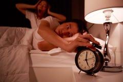 Pares soñolientos en cama con la mano que extiende al despertador en el m Fotos de archivo libres de regalías
