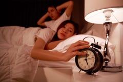 Pares soñolientos en cama con la mano que extiende al despertador en el m Fotos de archivo