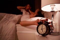 Pares soñolientos en cama con la mano que extiende al despertador en el m Fotografía de archivo