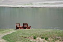 Pares solos de bancos de madera que esperan pacientemente al lado del agua foto de archivo