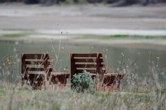 Pares solos de bancos de madera que esperan pacientemente al lado del agua imagenes de archivo