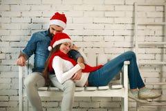 Pares sonhadores nos chapéus vermelhos do Natal que sentam-se no banco Fotografia de Stock