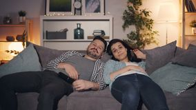 Pares sonolentos que olham a tevê em casa tarde no encontro de bocejo da noite no sofá junto filme
