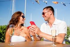 Pares sonrientes con champán y el regalo en el café Foto de archivo libre de regalías