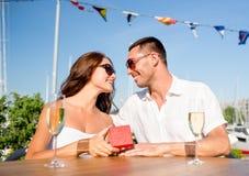 Pares sonrientes con champán y el regalo en el café Imagenes de archivo