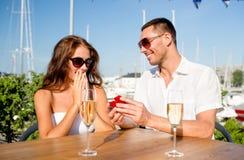 Pares sonrientes con champán y el regalo en el café Fotografía de archivo libre de regalías