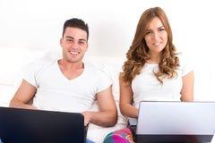 Pares sonrientes con dos ordenadores portátiles en cama Fotos de archivo