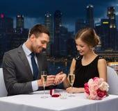Pares sonrientes con el anillo de bodas en el restaurante Fotos de archivo
