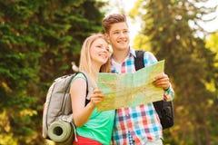 Pares sonrientes con el mapa y mochila en bosque Imagenes de archivo