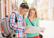 Pares sonrientes con el mapa y mochila en ciudad Fotos de archivo libres de regalías