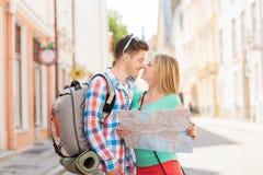 Pares sonrientes con el mapa y mochila en ciudad Fotografía de archivo libre de regalías