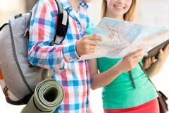 Pares sonrientes con el mapa y mochila en ciudad Imagen de archivo