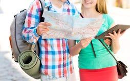 Pares sonrientes con el mapa y mochila en ciudad Imagenes de archivo