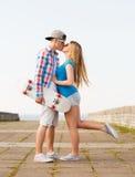 Pares sonrientes con el monopatín que se besa al aire libre Imagen de archivo libre de regalías
