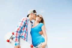 Pares sonrientes con el monopatín que se besa al aire libre Fotos de archivo libres de regalías