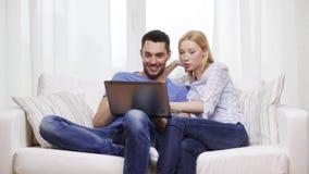 Pares sonrientes con el ordenador portátil en casa almacen de video