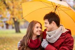 Pares sonrientes con el paraguas en parque del otoño Fotos de archivo