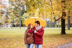 Pares sonrientes con el paraguas en parque del otoño Imagenes de archivo