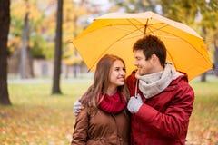 Pares sonrientes con el paraguas en parque del otoño Fotografía de archivo
