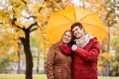 Pares sonrientes con el paraguas en parque del otoño Imagen de archivo libre de regalías