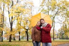 Pares sonrientes con el paraguas en parque del otoño Fotos de archivo libres de regalías