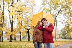 Pares sonrientes con el paraguas en parque del otoño Fotografía de archivo libre de regalías