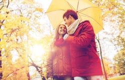Pares sonrientes con el paraguas en parque del otoño Imagen de archivo