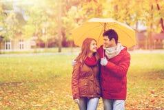 Pares sonrientes con el paraguas en parque del otoño Imágenes de archivo libres de regalías