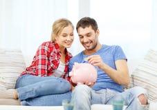 Pares sonrientes con el piggybank que se sienta en el sofá Imágenes de archivo libres de regalías