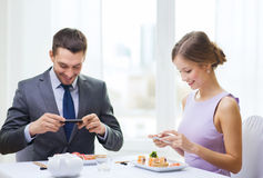 Pares sonrientes con el sushi y smartphones Imagen de archivo libre de regalías