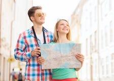 Pares sonrientes con la cámara del mapa y de la foto en ciudad Fotos de archivo libres de regalías