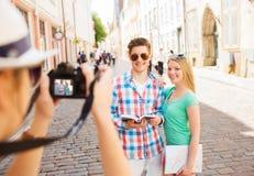 Pares sonrientes con la cámara del mapa y de la foto en ciudad Foto de archivo