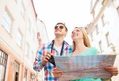 Pares sonrientes con la cámara del mapa y de la foto en ciudad Imágenes de archivo libres de regalías