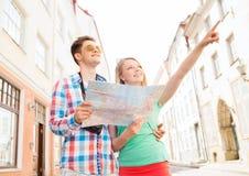 Pares sonrientes con la cámara del mapa y de la foto en ciudad Imagenes de archivo