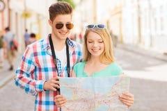 Pares sonrientes con la cámara del mapa y de la foto en ciudad Fotografía de archivo libre de regalías