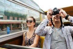 Pares sonrientes con la cámara que viaja en bus turístico Imagen de archivo