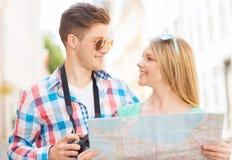 Pares sonrientes con la cámara del mapa y de la foto en ciudad Imagen de archivo libre de regalías