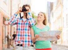 Pares sonrientes con la cámara del mapa y de la foto en ciudad Fotografía de archivo