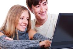 Pares sonrientes con la computadora portátil Imágenes de archivo libres de regalías