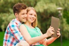 Pares sonrientes con la PC de la tableta que hace el selfie Foto de archivo
