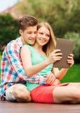 Pares sonrientes con la PC de la tableta que hace el selfie Imagenes de archivo