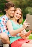 Pares sonrientes con la PC de la tableta que hace el selfie Foto de archivo libre de regalías