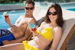 Pares sonrientes con las bebidas que se sientan por la piscina Foto de archivo