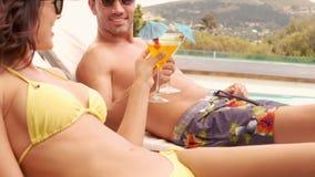 Pares sonrientes con las bebidas que sientan la piscina próxima metrajes