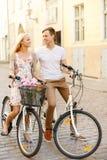 Pares sonrientes con las bicicletas en la ciudad Fotografía de archivo