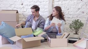 Pares sonrientes con las cajas de cartón que se mueven al nuevo hogar almacen de metraje de vídeo
