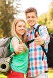 Pares sonrientes con las mochilas que muestran los pulgares para arriba Imágenes de archivo libres de regalías