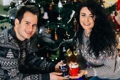 Pares sonrientes con las tazas de la melcocha del chocolate caliente fotografía de archivo libre de regalías