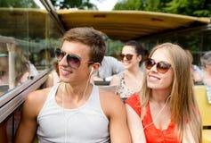Pares sonrientes con los auriculares que viajan en autobús Foto de archivo