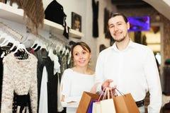 Pares sonrientes con los bolsos en el boutique de la ropa Foto de archivo